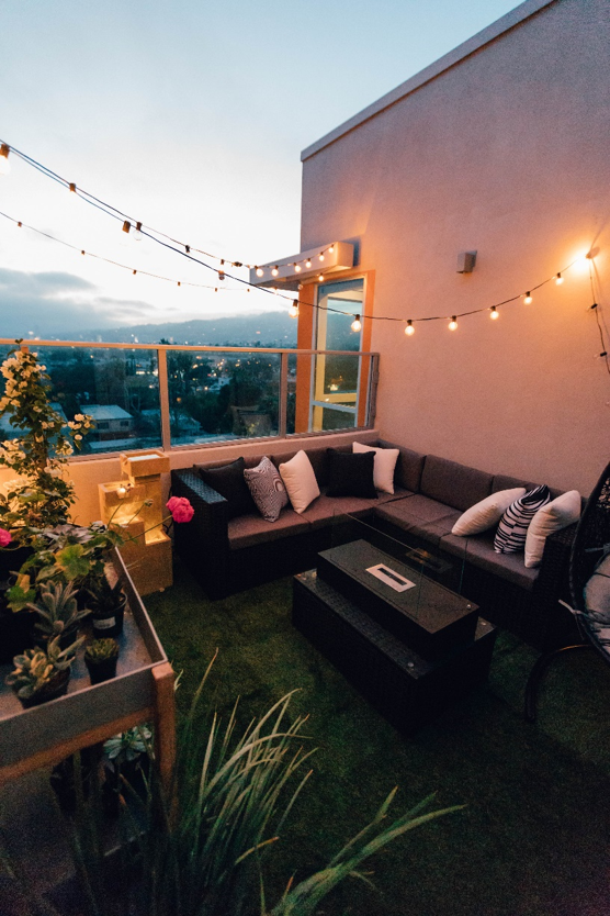 balkon met kunstgras, ingericht met lounge set, planten en lampjes.